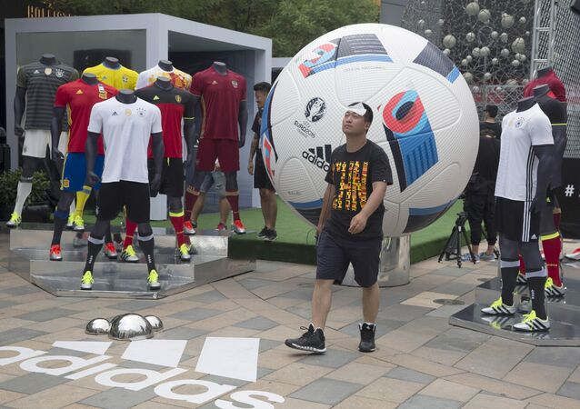 A man walks past a sports clothing promotion for the Euro 2016 tournament at a retail district in Beijing, China, Friday, June 10, 2016