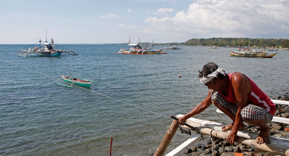 A fisherman repairs his boat overlooking fishing boats that fish in the disputed Scarborough Shoal in the South China Sea, at Masinloc, Zambales, in the Philippines (File)