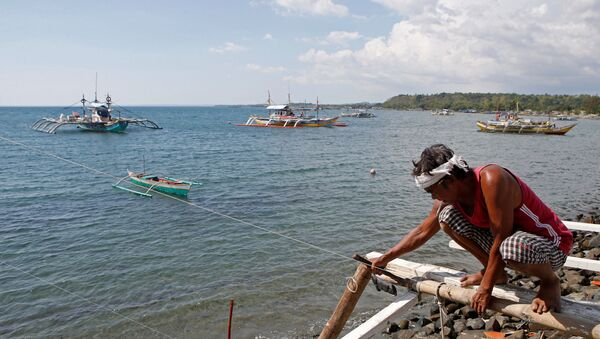 A fisherman repairs his boat overlooking fishing boats that fish in the disputed Scarborough Shoal in the South China Sea, at Masinloc, Zambales,in the Philippines. file photo - Sputnik International