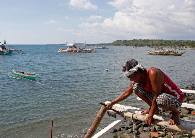 A fisherman repairs his boat overlooking fishing boats that fish in the disputed Scarborough Shoal in the South China Sea, at Masinloc, Zambales, the Philippines (File)