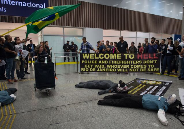 Police officers and firemen welcome passengers with a banner reading Welcome to Hell as they protest against the government for delay in their salary payments at Tom Jobim International Airport in Rio de Janeiro, Brazil, July 4, 2016