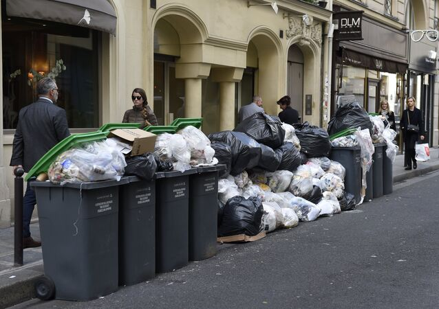 Pedestrians walk past unemptied garbage bins and plastic bags during a strike of garbage collectors in a street in Paris (File)