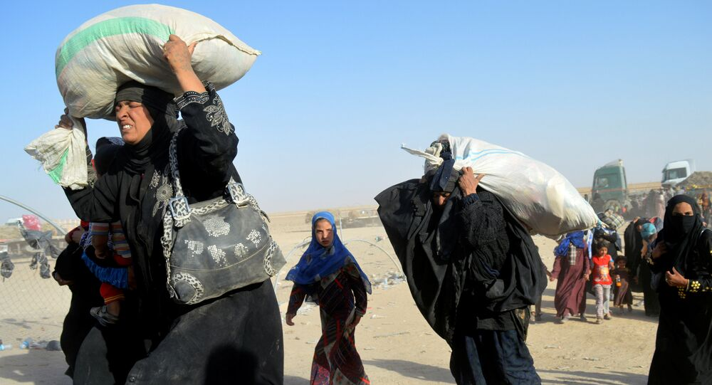 Women displaced by violence from Islamic State militants, arrive at a military base in Ramadi, Iraq.