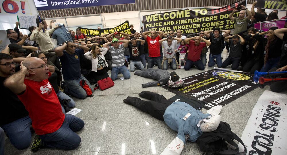 Police officers make a surrender position during a protest, demanding their payments and better labor conditions, at the Tom Jobim International Airport, in Rio de Janeiro, Brazil, Monday, July 4, 2016