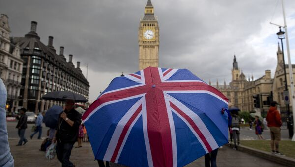 A pedestrian shelters from the rain beneath a Union flag themed umbrella as they walk near the Big Ben clock face and the Elizabeth Tower at the Houses of Parliament in central London on June 25, 2016. - Sputnik International