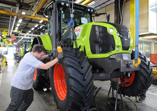 A worker adjusts the front wheel of a tractor on the assembly line of the Claas tractor manufacturer plant (File)