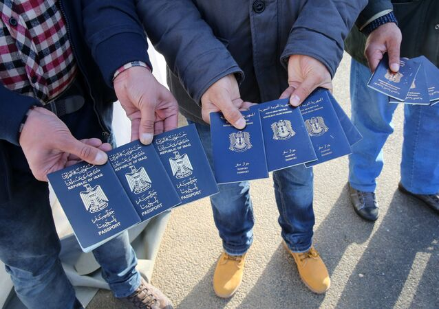Migrants show passports from Iraqi and Syrian fellow travellers they have to present to buy ferry tickets for their passage to Sweden
