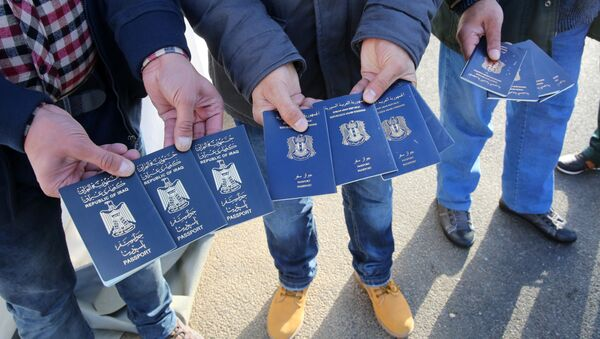 Migrants show passports from Iraqi and Syrian fellow travellers they have to present to buy ferry tickets for their passage to Sweden - Sputnik International