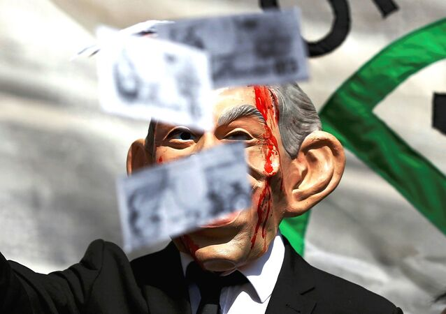 A demonstrator wearing a mask to impersonate Tony Blair holds throws fake money during a protest before the release of the John Chilcot report into the Iraq war, at the Queen Elizabeth II center in London, Britain July 6, 2016.