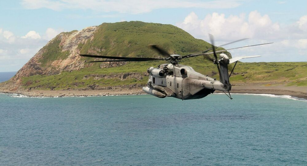 A CH-53E Super Stallion from Marine Medium Tiltrotor Squadron 163 (Reinforced), 11th Marine Expeditionary Unit, flies past Mount Suribachi at Iwo To, Japan.