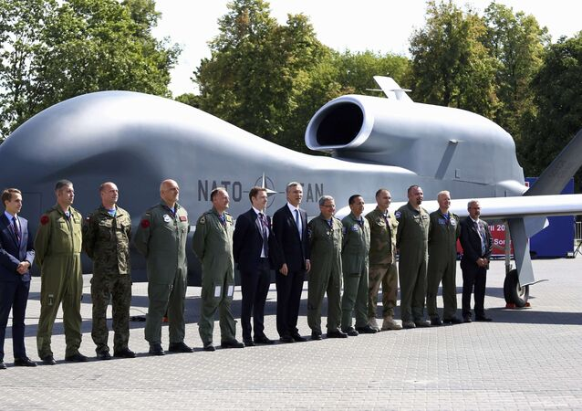 NATO Secretary-General Jens Stoltenberg (C) poses with officials and military personnel in front of a NATO unmanned drone outside PGE National Stadium, the venue of the NATO Summit, in Warsaw, Poland, July 8, 2016.