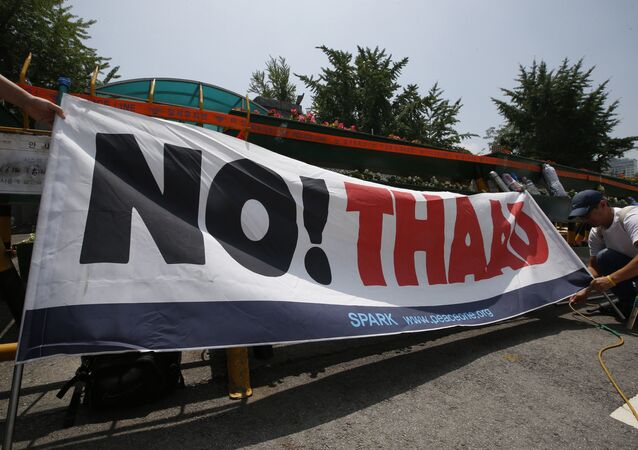 A South Korean protester ties a banner before a rally to denounce deploying the Terminal High-Altitude Area Defense, or THAAD, in front of the Defense Ministry in Seoul, South Korea, Friday, July 8, 2016.