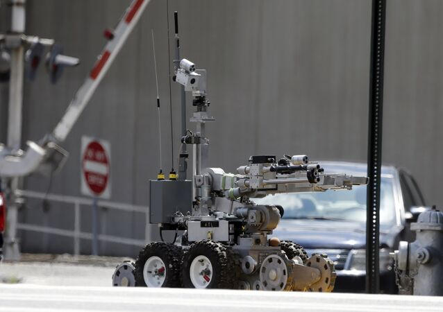 An Atlanta Police robot loads a possible Civil-War era cannonball into an explosives containment vehicle.