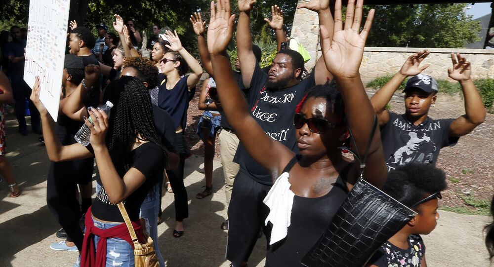 People march holding their hands in the air in protest as they walk through Smith Park in downtown Jackson, Miss., Friday afternoon, July 8, 2016.