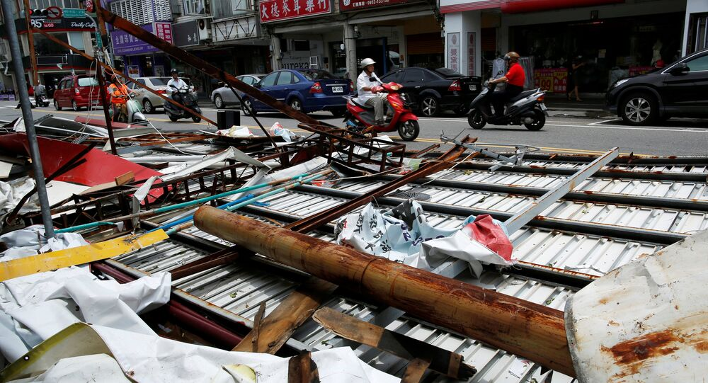 Motorcyclists ride past advertisement banners damaged by Typhoon Nepartak, in Taitung, Taiwan July 9, 2016