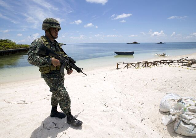 A Filipino soldier patrols at the shore of Pagasa island (Thitu Island) in the Spratly group of islands in the South China Sea, west of Palawan, Philippines, May 11, 2015