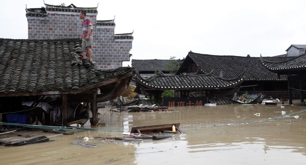 Man standing on the rood of a flood-inundated building in the flooded ancient town of Longshan county, central China's Hunan province
