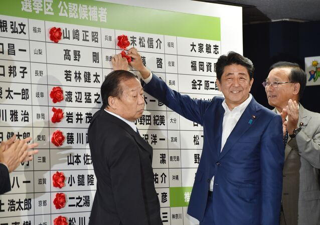 Japanese Prime Minister and ruling Liberal Democratic Party (LDP) president Shinzo Abe (C) places a red paper rosette on an LDP candidate's name to indicate an election victory at the party's headquarters in Tokyo on July 10, 2016