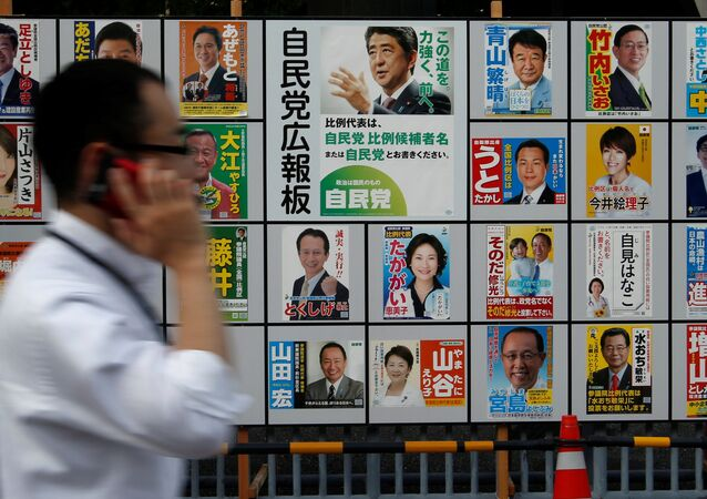 A man walks past Japan's ruling Liberal Democratic Party's (LDP) poster (C) for the July 10 upper house election with the image of Shinzo Abe, Japan's Prime Minister and leader of the LDP, and other candidates' posters at the LDP headquarters in Tokyo, Japan July 10, 2016