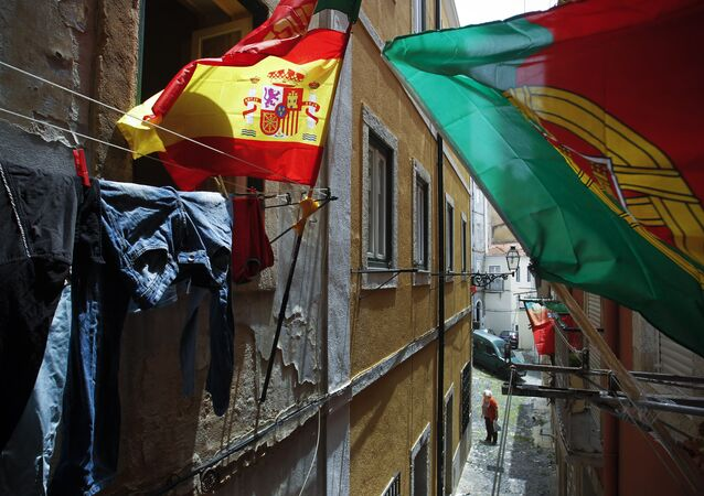 Portugal and Spain's flags wave at the balconies of a narrow street of Lisbon's Mouraria neighborhood (File)