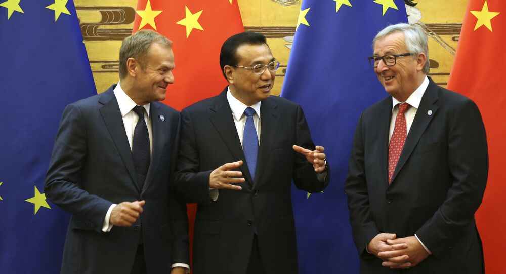 Chinese Premier Li Keqiang, center, gestures to European Council President Donald Tusk, left, and European Commission President Jean-Claude Juncker during a signing ceremony at an EU-China Summit meeting in the Great Hall of the People in Beijing Tuesday, July 12, 2016