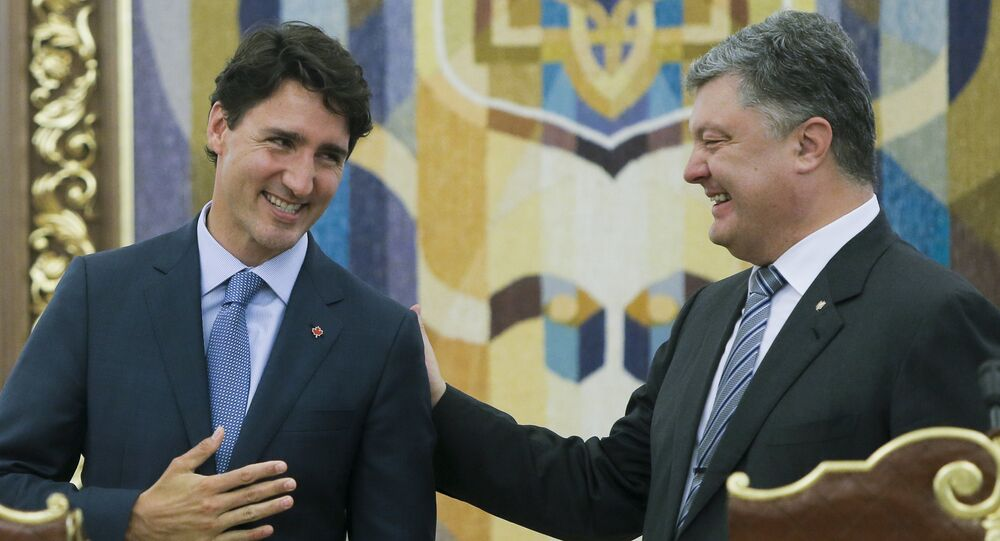 Ukrainian President Petro Poroshenko, right, and Canadian Prime Minister Justin Trudeau smile as they talk to each other during a signing ceremony in Kiev, Ukraine, Monday, July 11, 2016