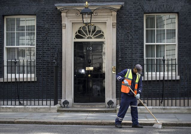 A workman cleans the street outside 10 Downing Street in London on July 12, 2016, as Prime Minister David Cameron chairs his last Cabinet meeting