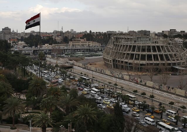 A Syrian national flag waves as vehicles move slowly in a traffic jam during rush hours on a road in Damascus , Syria (File)