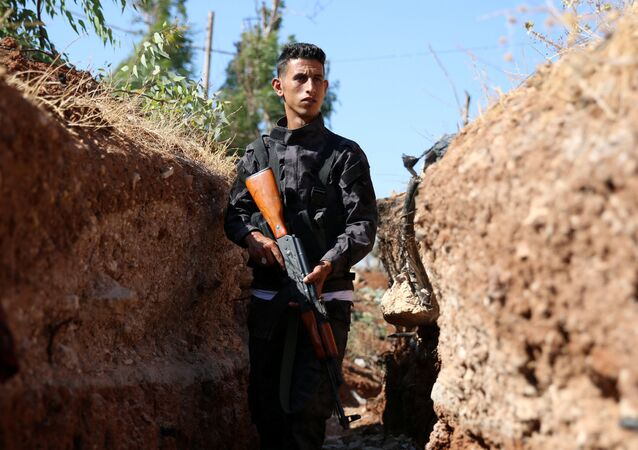 A Free Syrian Army fighter carries his weapon inside a trench in Al-Yadudah village, in Deraa Governorate, Syria July 8, 2016.