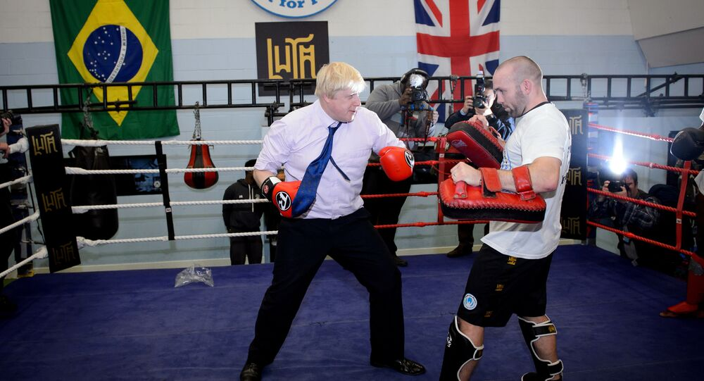 Mayor of London Boris Johnson (L) boxes with a trainer during his visit to Fight for Peace Academy in North Woolwich, London, on October 28, 2014