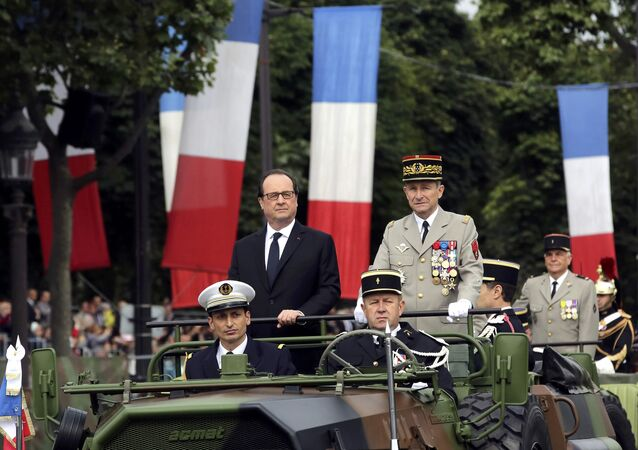 French President Francois Hollande (L) and Chief of the Defense Staff French Army General Pierre de Villiers arrive in a command car for the annual Bastille Day military parade on the Champs Elysees avenue in Paris, France, July 14, 2016.