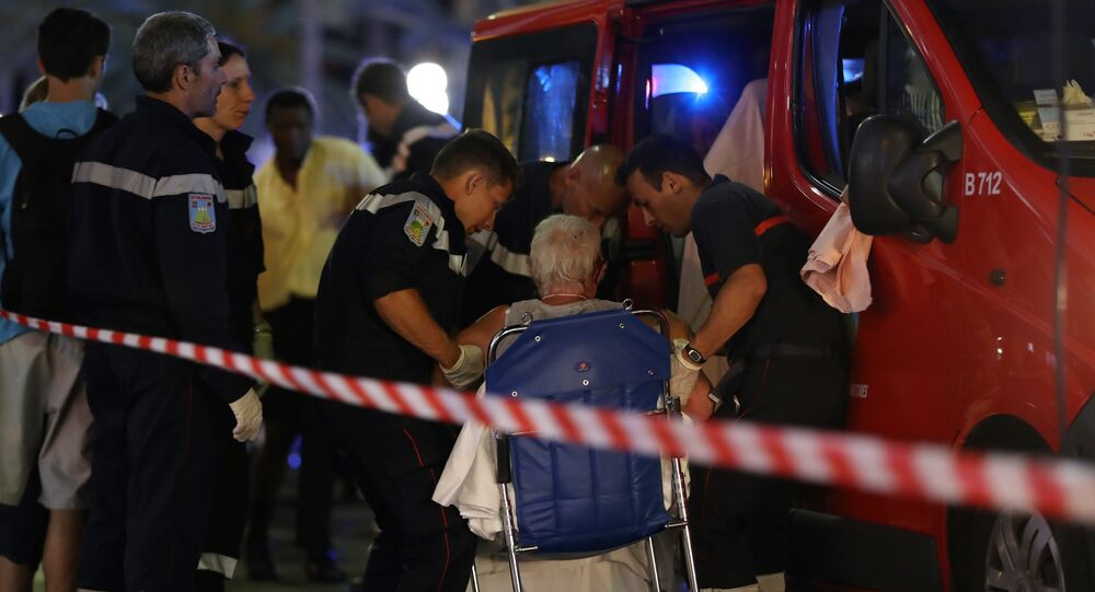 Rescue workers help an injured woman to get in a ambulance on July 15, 2016, after a truck drove into a crowd watching a fireworks display in the French Riviera town of Nice.