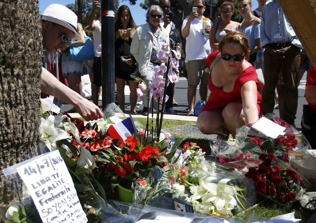 A woman places a bouquet of flowers as people pay tribute near the scene where a truck ran into a crowd at high speed killing scores and injuring more who were celebrating the Bastille Day national holiday, in Nice, France, July 15, 2016.