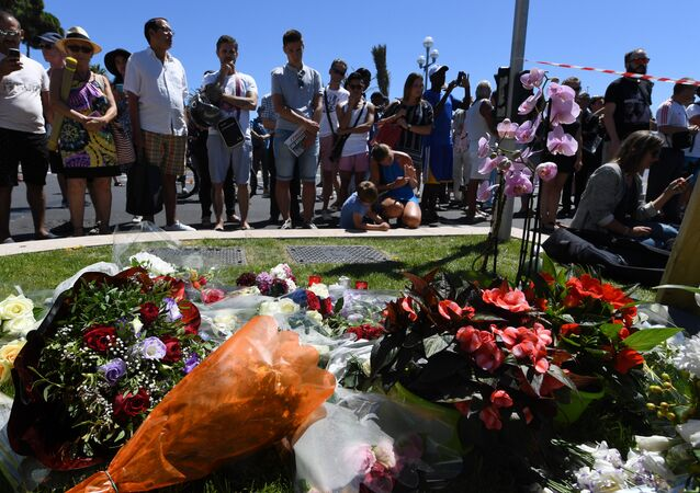People stand on July 15, 2016 in front of flowers and candles placed near the site in Nice where a gunman smashed a truck into a crowd of revellers celebrating Bastille Day, killing at least 84 people.