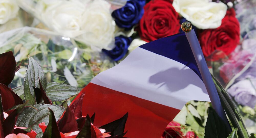 A bouquet of flowers and a French flag is seen as people pay tribute near the scene where a truck ran into a crowd at high speed killing scores and injuring more who were celebrating the Bastille Day national holiday, in Nice, France, July 15, 2016.