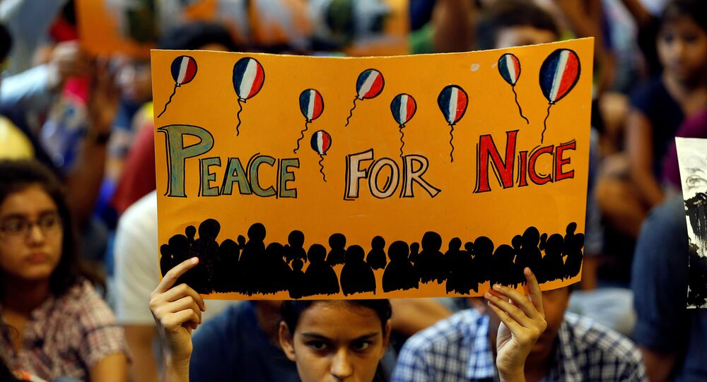 A girl holds up a placard during a prayer meet to show solidarity with the victims of the Bastille Day truck attack in Nice, at a school in Ahmedabad, India, July 15, 2016.
