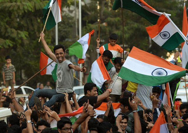 Indian fans wave national flags as they celebrate after India won the 2015 Cricket World Cup's cricket match against Pakistan, on the streets of Mumbai
