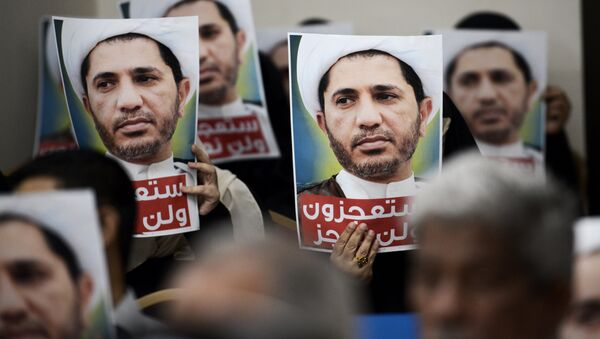 Bahraini men hold placards bearing the portrait of Sheikh Ali Salman, head of the Shiite opposition movement Al-Wefaq, during a protest on May 29, 2016 against his arrest, at Al wefaq headquarter building, in the village of Zinj on the outskirts of the capital Manama. - Sputnik International