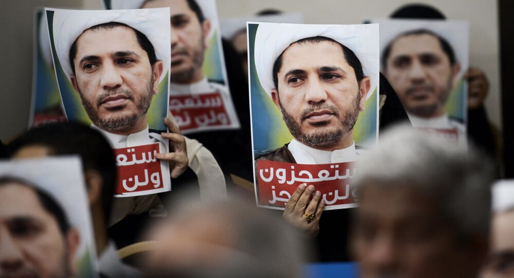 Bahraini men hold placards bearing the portrait of Sheikh Ali Salman, head of the Shiite opposition movement Al-Wefaq, during a protest on May 29, 2016 against his arrest, at Al wefaq headquarter building, in the village of Zinj on the outskirts of the capital Manama.
