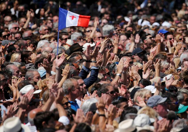 A French flag flies among the crowd as people applaud in front of the Monument du Centenaire during a minute of silence on the third day of national mourning to pay tribute to victims of the truck attack along the Promenade des Anglais on Bastille Day that killed scores and injured as many in Nice, France, July 18, 2016.