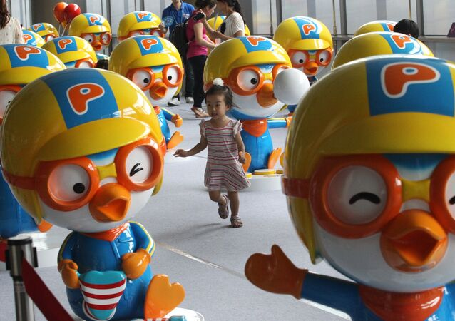 A girl passes by dolls featuring South Korean animation character Pororo displayed at a character licensing show in Seoul, South Korea, Friday, July 19, 2013