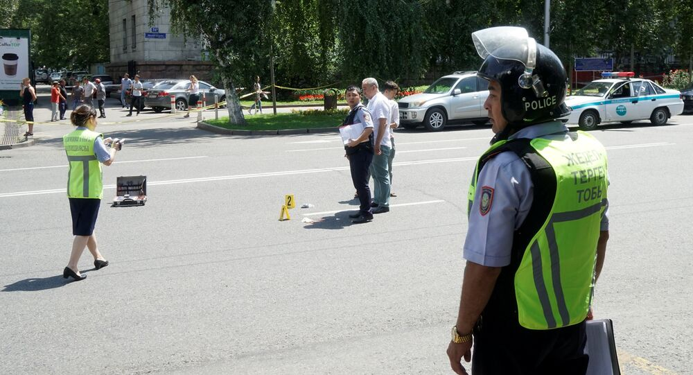 Investigators and police officers work on a scene of shooting on the street in Almaty, Kazakhstan, July 18, 2016