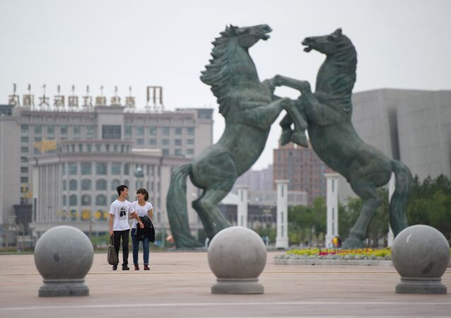 A photo taken on August 18, 2012 shows a couple walking past a statue in Genghis Khan Plaza, in the inner Mongolian city of Ordos