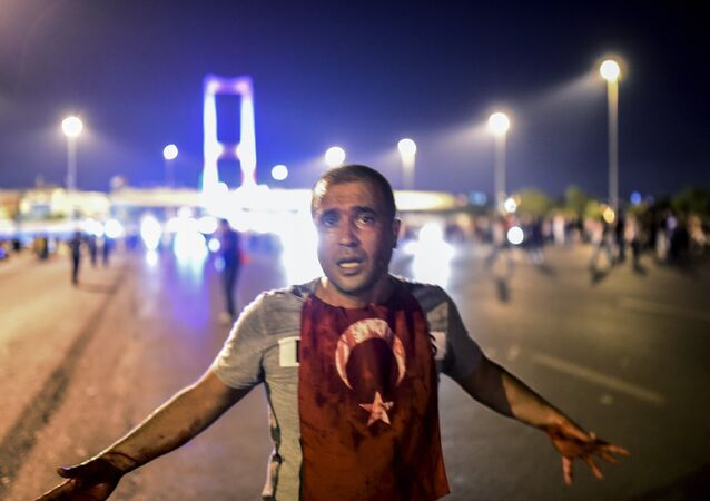 A man covered with blood stands near the Bosphorus bridge as Turkish military clash with people at the entrance to the bridge in Istanbul on July 16, 2016