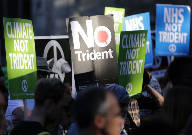 Demonstrators hold placards calling for government funds to be spent on the NHS and climate change, as they attend an anti-war and anti-trident demonstration near the Houses of Parliament in central London on July 18, 2016