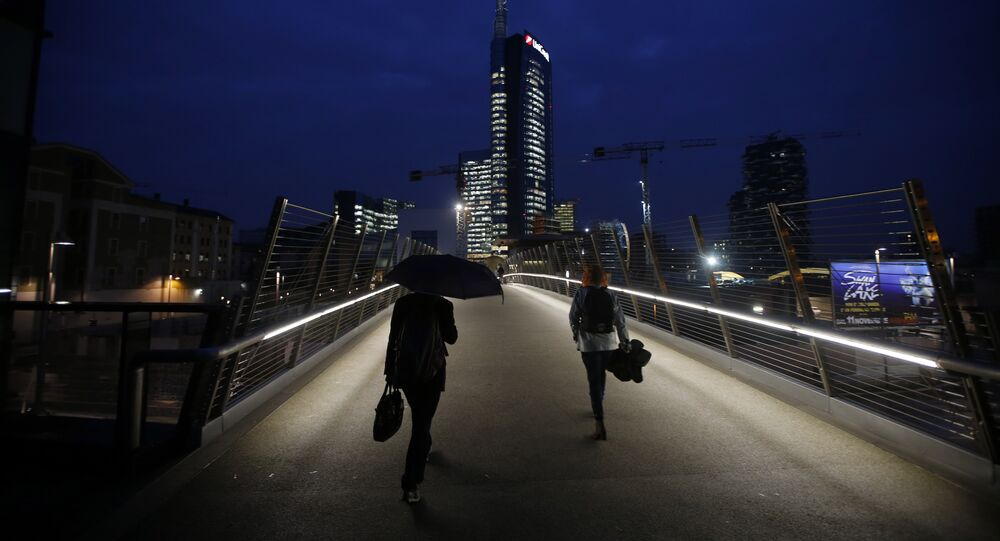 People walk on a bridge which leads to business center and the Unicredit headquarters building, center, in Milan, Italy (File)