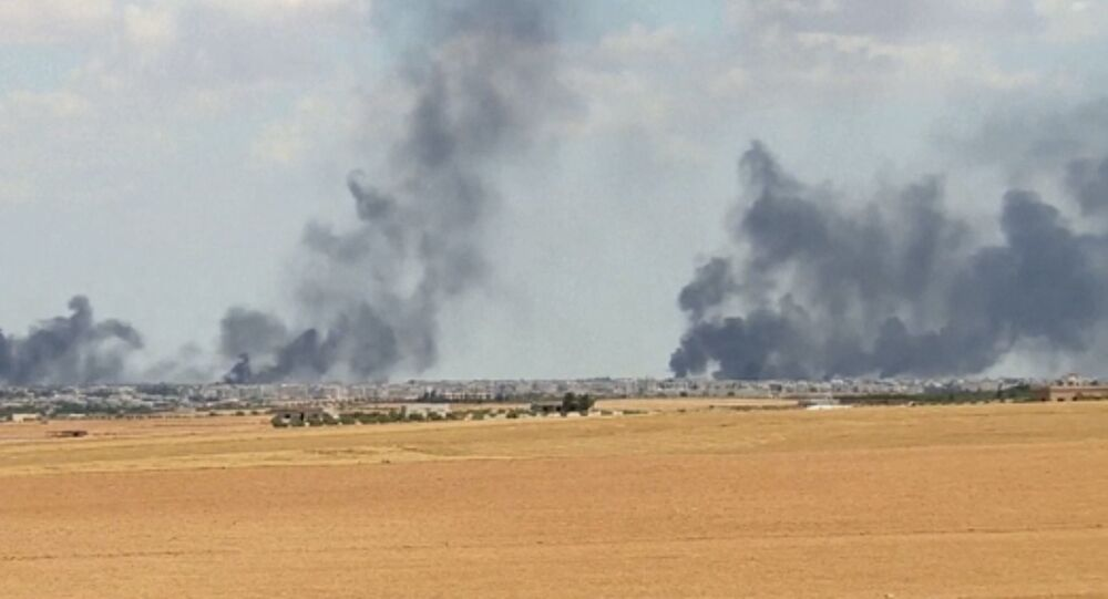 A video grab shows smoke rising from the city of Manbij, Syria.