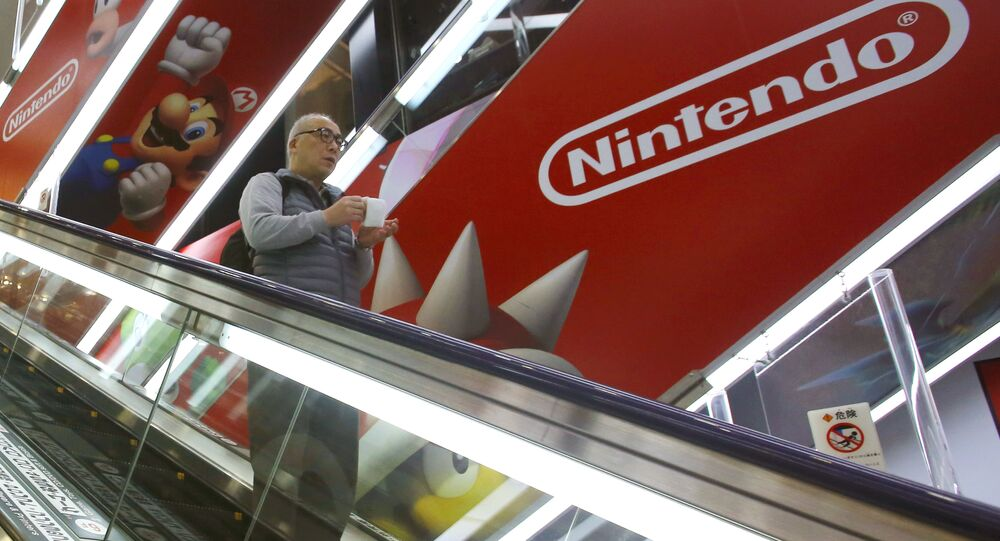 In this March 20, 2016, file photo, a shopper standing on an escalator passes by the Nintendo logo at an electronics store in Tokyo