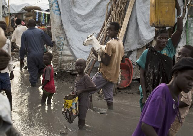 South-Sudanese man carries a goat as he and others wade through mud-filled paths between makeshift tents in the United Nations base (File)