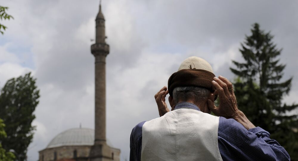 An elderly Kosovo Muslim prays on the street in front of a mosque during Friday Prayer on July 1, 2011 in Pristina